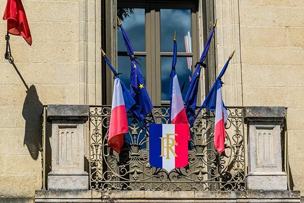 drapeaux en berne devant une façade de mairie