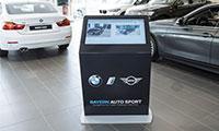 borne tactile installée dans une concession automobile